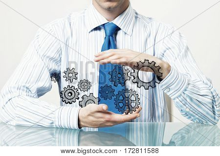 Close up of businessman sitting at table and protecting gear mechanism with palms.