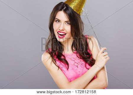 Lovely young girl with dark hair and red lips wearing pink dress posing with magic stick at gray studio background, portrait.