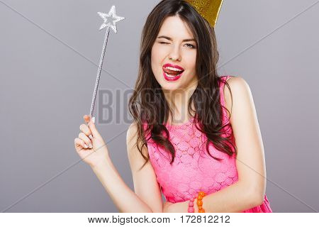 Nice young girl with dark hair and red lips wearing pink dress posing with magic stick at gray studio background, portrait, copy space.