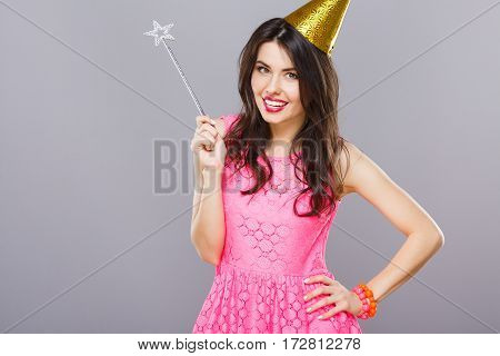 Pretty young girl with dark hair and red lips wearing pink dress posing with magic stick at gray studio background, portrait.