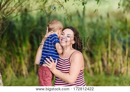 Happy mother and her son hugging. Green background blurred, outdoors.