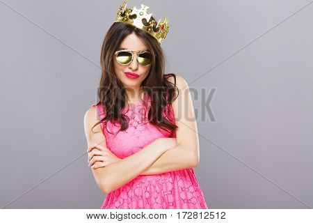 Attractive young girl with dark hair and red lips wearing pink dress, sunglasses and crown posing at gray studio background, portrait.