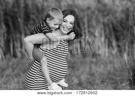 Child sitting on the shoulders of his pregnant mother. Happy mother and her son. Green background blurred, outdoors. Black and white photo.