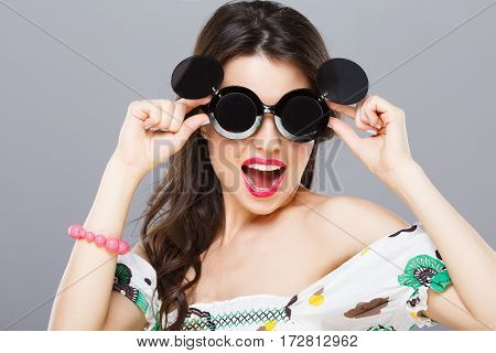 Beautiful girl in black round sunglasses with side glasses. Looking at camera, opened mouth. Touching glasses. Summer outfit, floral dress. Head and shoulders, studio, indoors