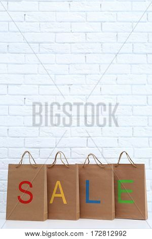 Colorful word SALE on paper shopping bags against brick wall background