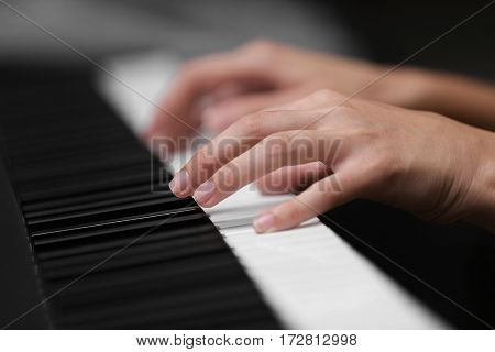 Female hands playing on synthesizer, closeup