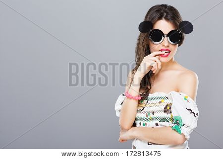 Beautiful girl in black round sunglasses with side glasses. Looking at camera, finger between teeth. Summer outfit, floral dress. Waist up, studio, indoors