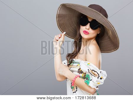 Beautiful girl in hat and black round sunglasses. Looking at camera, touching hat, kiss. Summer outfit, floral dress. Waist up, studio, indoors