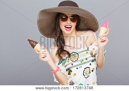 Beautiful girl in hat and sunglasses smiling widely. Holding two colorful ice-creams. Looking at camera, touching hair. Summer outfit, floral dress. Waist up, studio, indoors