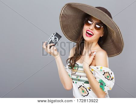 Beautiful girl in hat and sunglasses smiling widely. Holding camera. Looking at camera, touching hair. Summer outfit. Waist up, studio, indoors