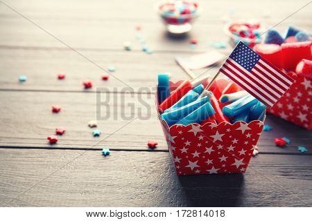 Delicious candies with USA flag in paper box on wooden background