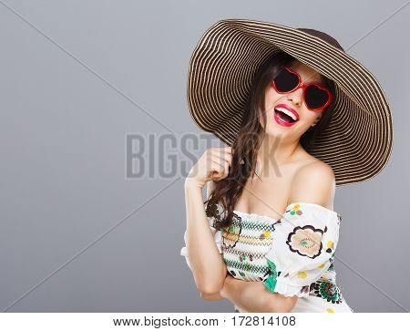 Beautiful girl in hat and heart-shaped sunglasses smiling widely. Looking at camera, touching hair. Summer outfit. Waist up, studio, indoors