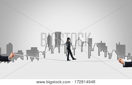 Businessman with blindfold on eyes walking on tightrope.