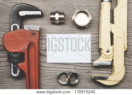 Pipes plumbing tools fittings and business card on the wooden surface background