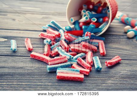 Assortment of delicious candies on wooden background