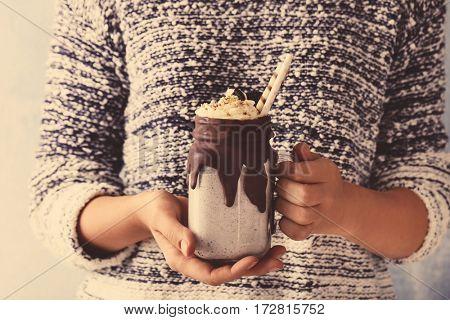 Woman holding tasty milkshake, closeup