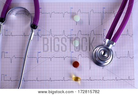 Stethoscope and some pills - isolated on a white background.