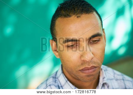 Real Cuban people and emotions portrait of sad latino man from Havana Cuba looking at camera with worried face and depressed expression