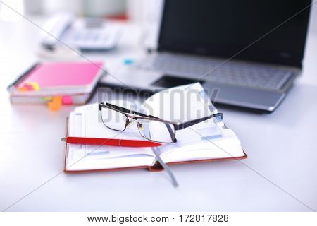 A note book, laptop, pen, graph paper document on the office desk table behind white blind.