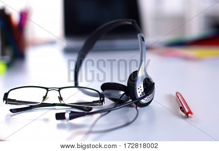 Headset on the table with notebook and pen.