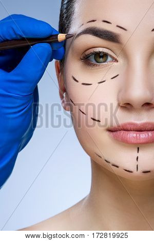 Young girl with dark eyebrows at studio background, doctor's hand making marks on patient's face, portrait, perforation lines on face, close up, portrait.