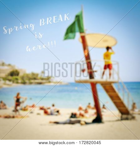 text spring break is here on a blurred picture of a beach full of unrecognizable people sunbathing