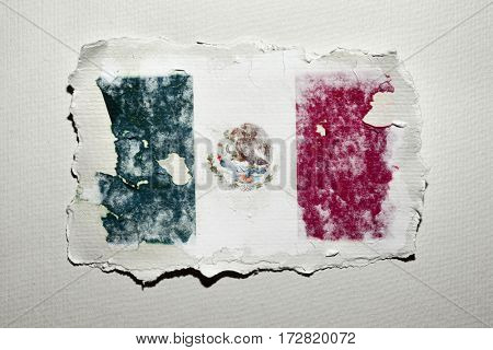 the flag of Mexico in an aged piece of paper on an off-white background