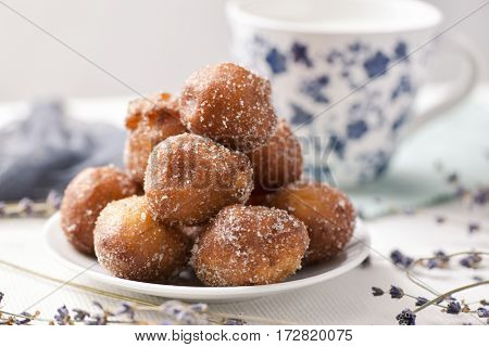 a pile of bunyols de Quaresma, typical pastries of Catalonia, Spain, eaten in Lent, on a white ceramic plate on a table set with a white tablecloth