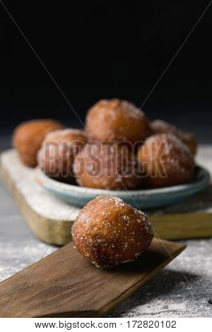 a pile of bunyols de Quaresma, typical pastries of Catalonia, Spain, eaten in Lent, on an earthenware plate on a rustic wooden table