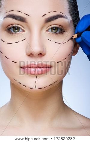 Young girl with dark eyebrows at studio background, doctor's hand making marks on patient's face, portrait, perforation lines on face.