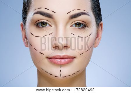 Pretty girl with dark hair looking at camera at gray studio background, perforation lines on face, portrait, close up.