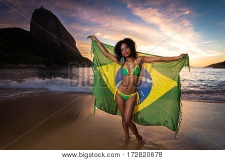 Young Beautiful and Sexy Girl in Bikini Holding Beach Yoke With Brazilian Flag by Sunrise with the Sugarloaf Mountain in the Background, in Rio de Janeiro