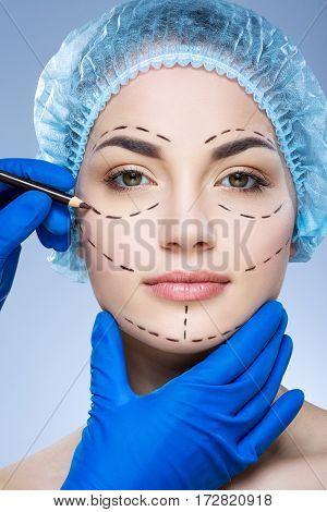 Perfect girl with dark eyebrows wearing blue medical hat at studio background, doctor's hand making marks on patient's face, portrait, perforation lines on face.