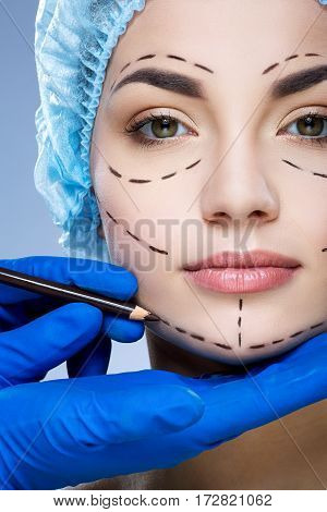 Pretty girl with dark eyebrows wearing blue medical hat at studio background, doctor's hand making perforation lines on patient's face.