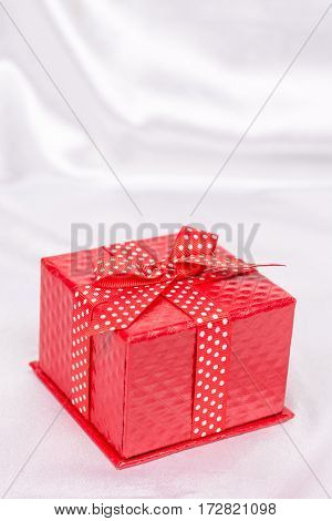 Red Gift Box With Bow On The White Satin Background