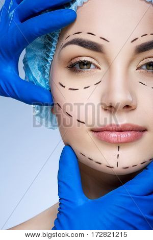 Cute girl with dark eyebrows wearing blue medical hat at studio background, doctor's hands showing on patient's face, perforation lines on face.