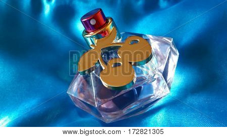 Beautiful perfume bottle on a blue silky background