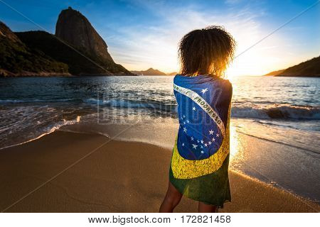 Girl With Curly Hair and Brazilian Flag on Her Back Standing in the Beach and Watching the Sunrise with the Sugarloaf Mountain in the Horizon, in Rio de Janeiro