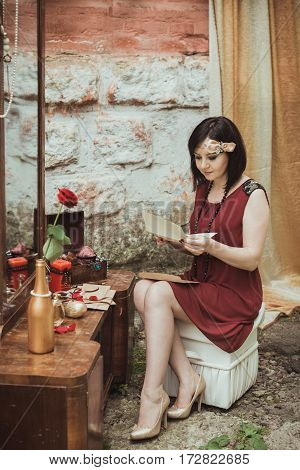 retro girl sitting at a dressing table and reading a letter