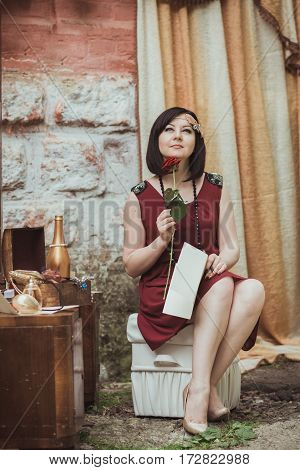 retro girl sitting at a dressing table with a letter and red rose in your hands