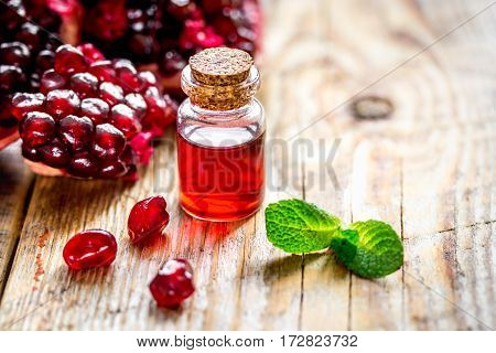 sliced pomegranate and extract in glass on wooden background close up