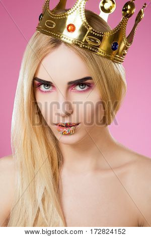 Beautiful young girl with big eyes, dark eyebrows, sweet lips and naked shoulders wearing crown and looking at camera at pink background, portrait.