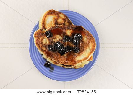 delicious pancakes with cherry jam on a blue plate