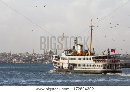 ISTANBUL TURKEY - DECEMBER 30 2015: Ferry leaving the port of Kadikoy district Asian side of the city heading to the European side Ayasofya mosque can be seen in the background