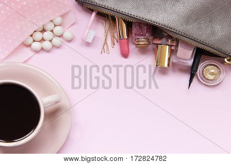 A make up bag spills open onto pink desk top with coffee and gumballs.