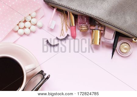 Beauty supplies strewn across a pink vanity with gumballs and coffee. Room for copy