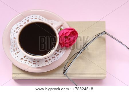 Top view pink background with coffee cup, doily, doily, flower, book and eyeglasses. Open space for copy