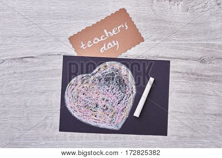 Card on Teacher's Day. Chalk heart near greeting paper. From students to teachers.