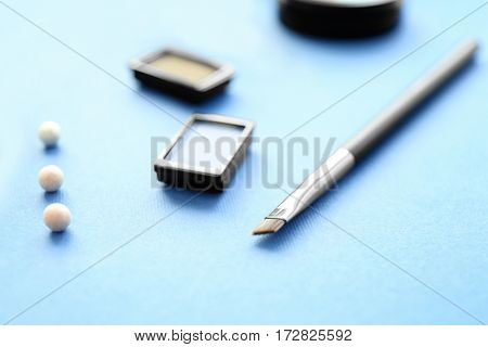 Brush and cosmetics on blue background, closeup