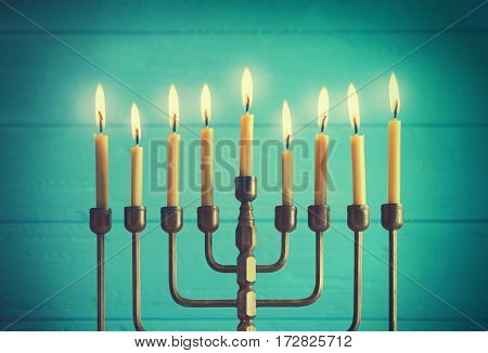 Menorah with candles for Hanukkah on blurred wooden background, closeup